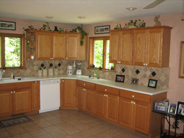 Oak Cabinets with Crown Molding, Custom Backsplash, & Tile Flooring